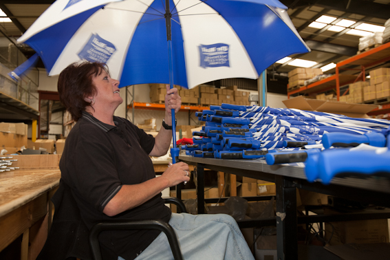 Woman holdin open umbrella in factory